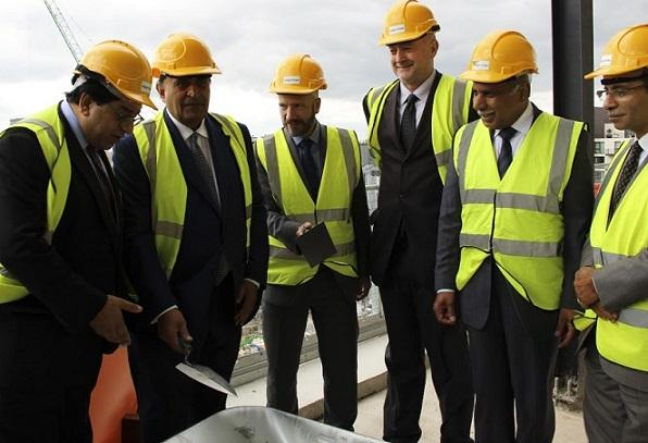 Representatives from AKDN, IIS Board of Governors, AKF UK and the Ismaili Council for the United Kingdom, adding cement to the final piece of the structure.